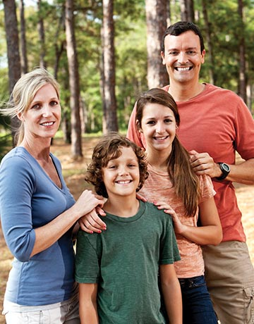 Family of four smiling with dense forest in background