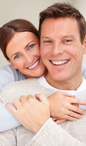 Couple in sweaters smiling at camera and embracing