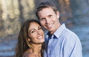 Couple in front of lake smiling at camera
