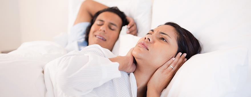 Woman holding her ears because of man's snoring