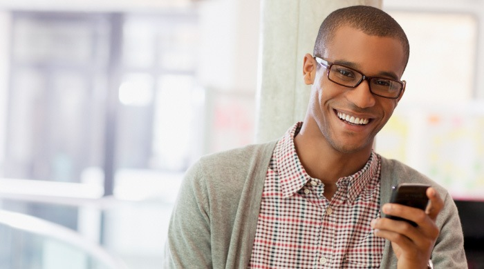 young man in glasses holding phone smiling