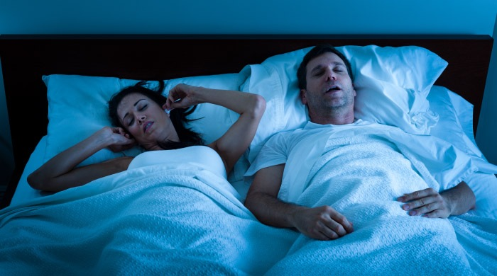 couple in bed man snoring because of sleep apnea woman covering her ears