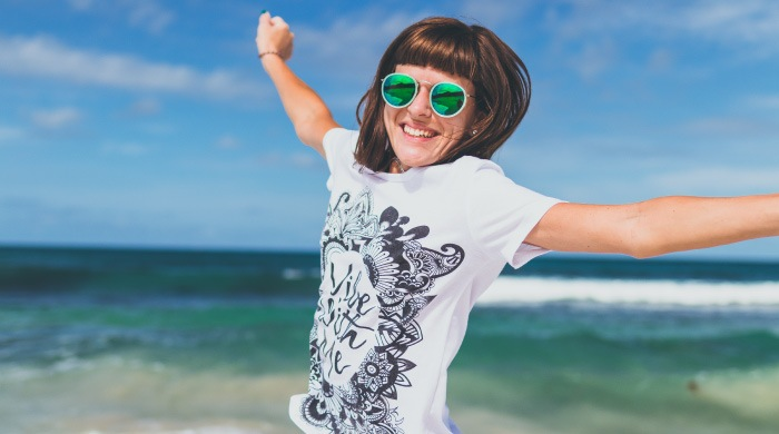 Brunette woman wearing a white t-shirt and sunglasses jumps into the air, arms outstretched, by the ocean