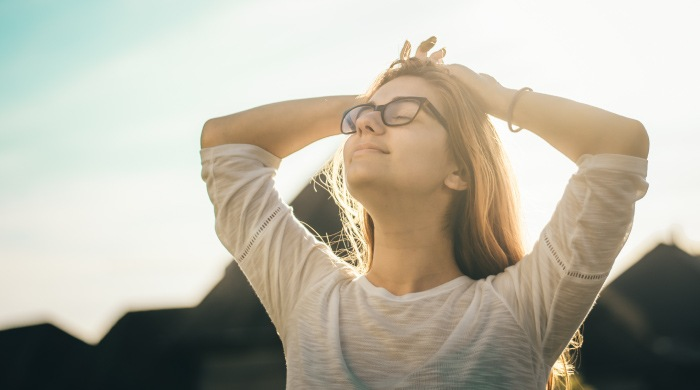 Relaxed young woman wearing glasses puts her hands on her head and breathes deeply with her chin up