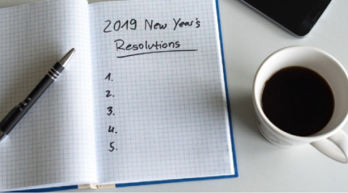 2019 new year's resolutions notebook, a cup of coffee and a pen