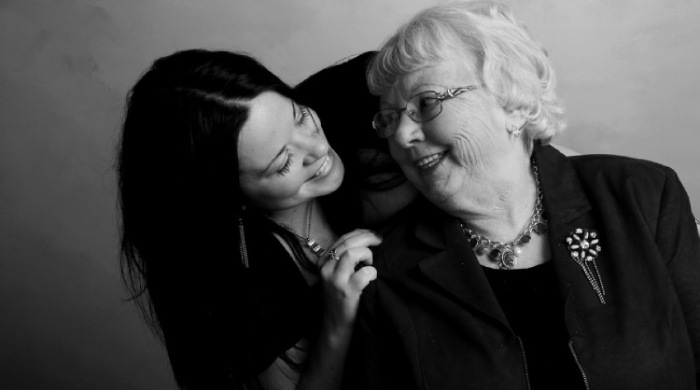 dark haired granddaughter leaning over embracing and smiling at her grandmother