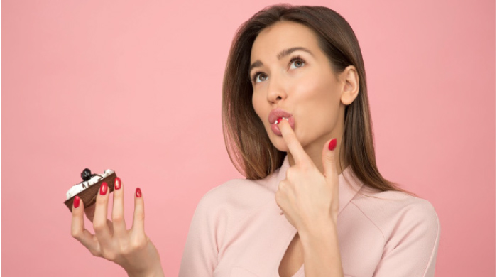 woman holding a donut licking frosting off her finger
