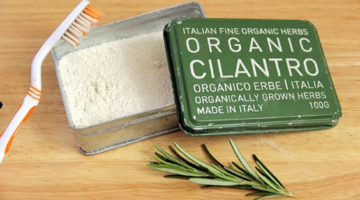 tin of organic toothpaste with a toothbrush
