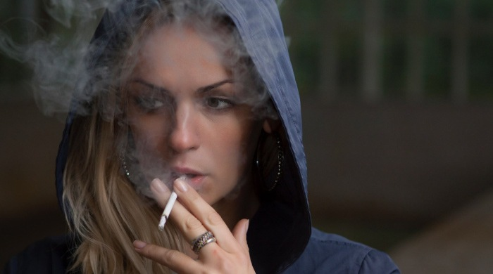 woman in a hoodie smoking a cigarette