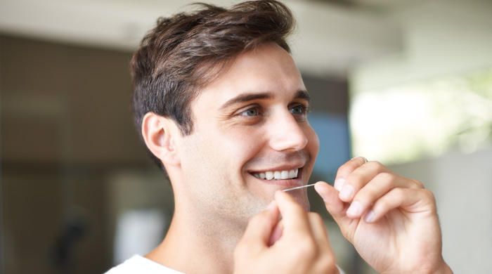 man flossing his teeth to prevent plaque buildup