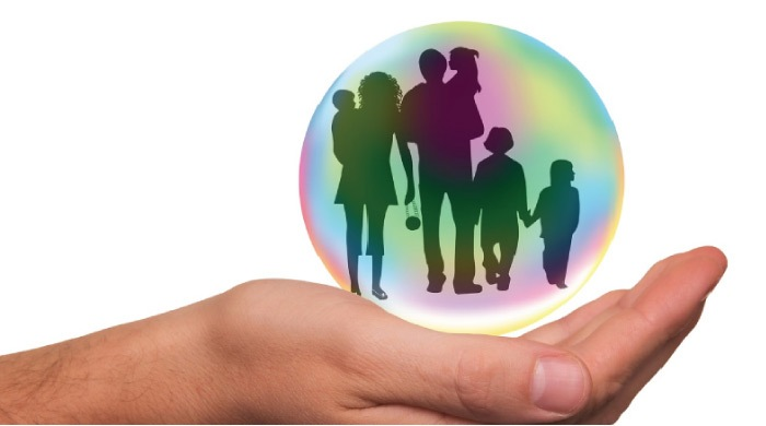 open hand holding a bubble with a family enclosed signifying insurance coverage