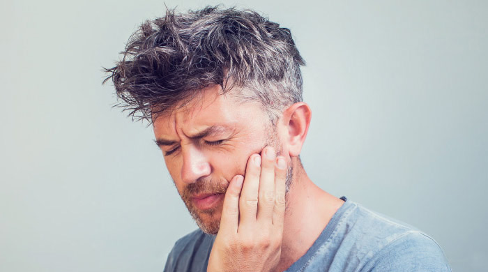 man holding his jaw and grimacing in pain