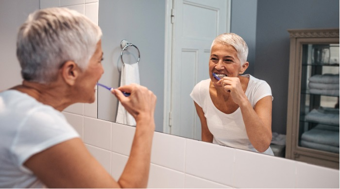 elderly woman brushing her teeth in front of a mirror
