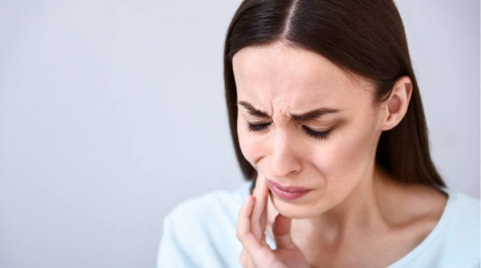 woman holding her jaw with painful gums