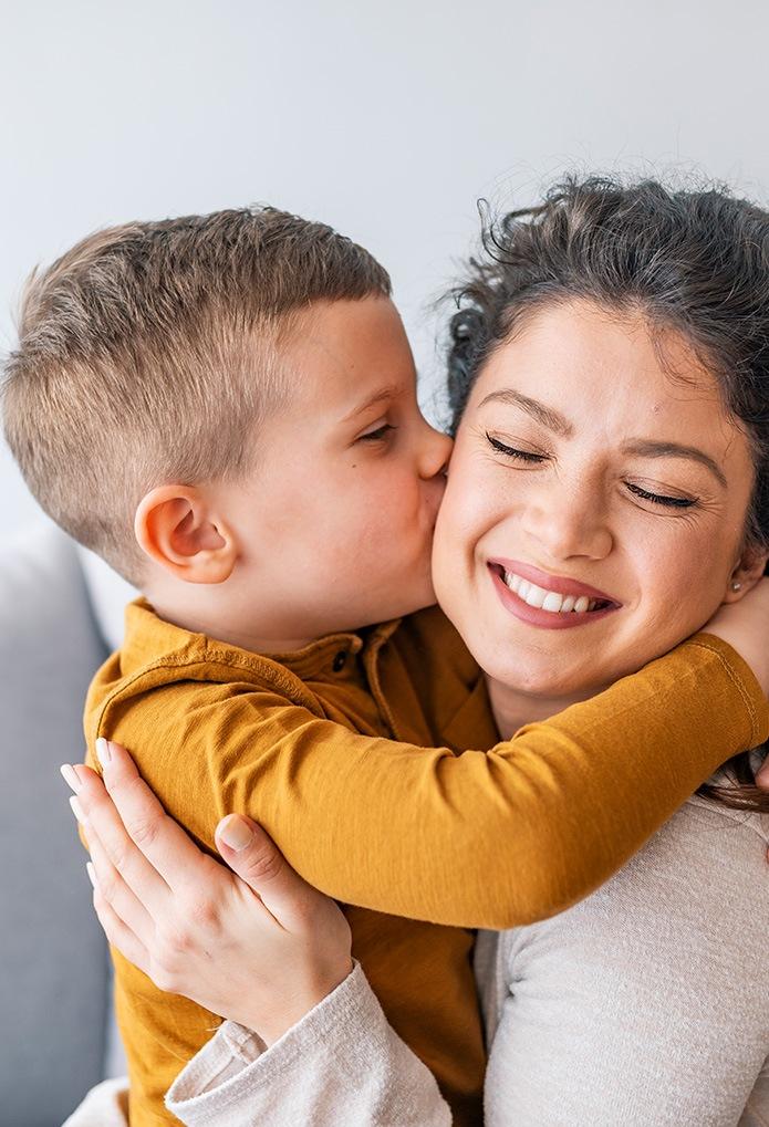 little boy kissing mom on the cheek