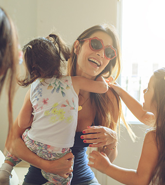 mom with sunglasses holding daughter