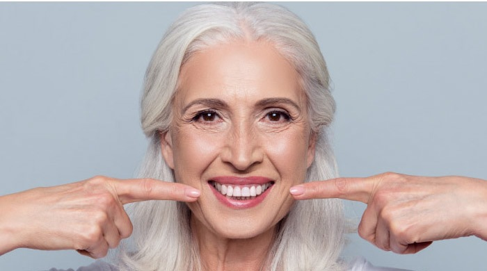 woman with long white hair smiles and points to her white teeth with both forefingers