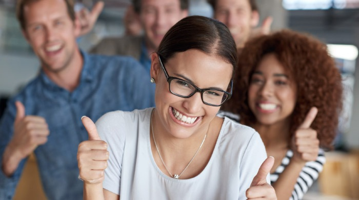 group of young adults give thumbs up to dental sealants for adults