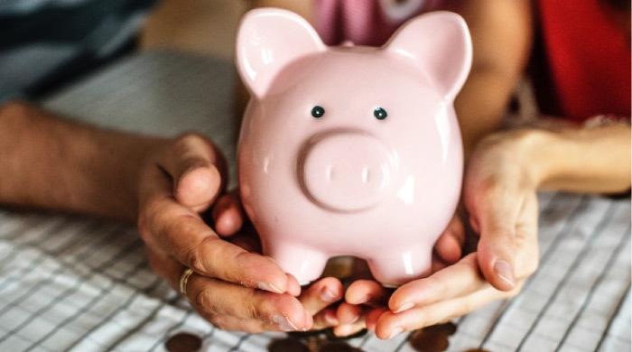 pink piggy bank spilling out coins