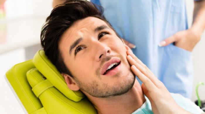 man in the dentist's chair holding his jaw before root canal therapy