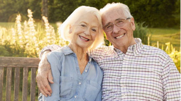 senior couple sitting on a bench hugging and smiling after learning their dental bridges can be repaired
