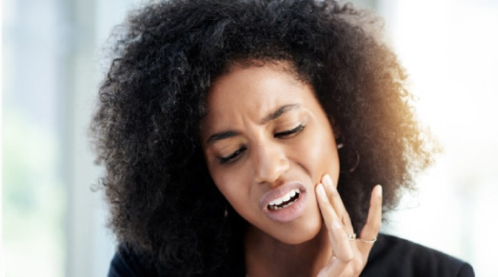 woman holding her jaw in pain needs a root canal