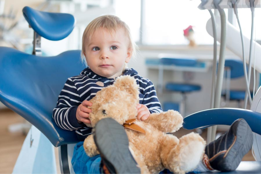 young child sitting in the dentist chair holding a stuffed bear
