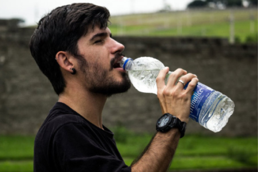 young man drinking a big bottle of water