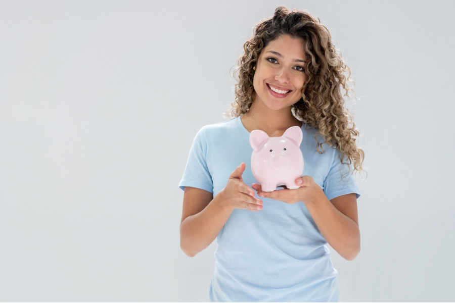 woman holding a piggybank and smiling about affordable dentistry