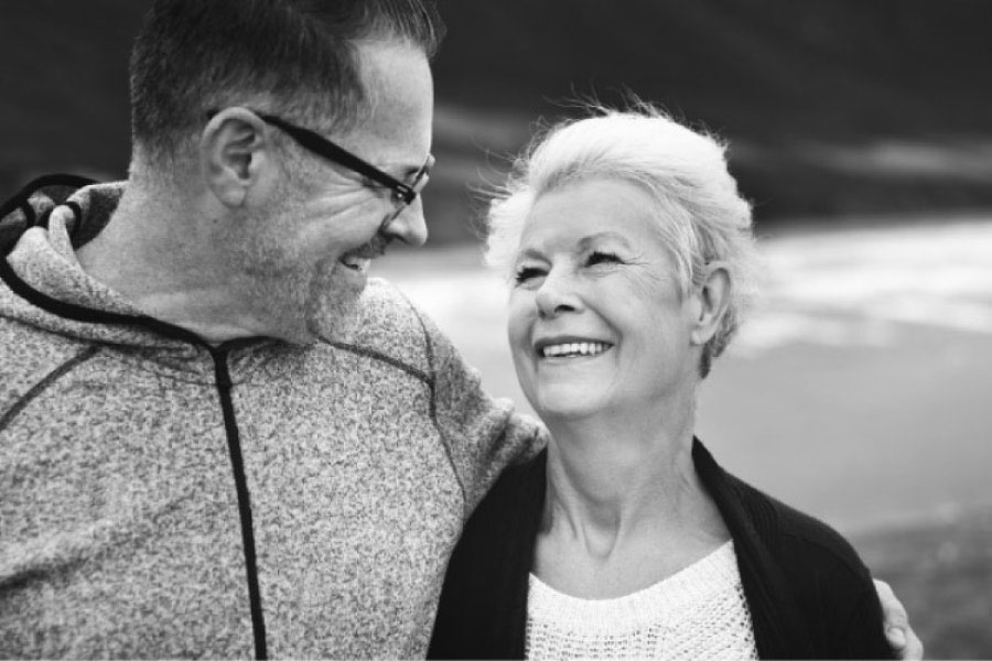 senior couple smile at each other after learning about dental bridges