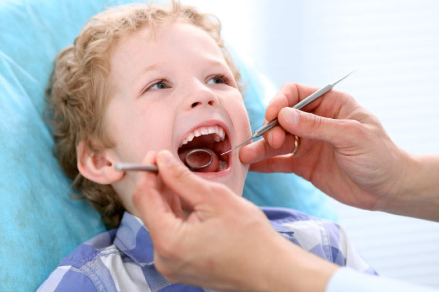 young boy with his mouth open getting a dental exam