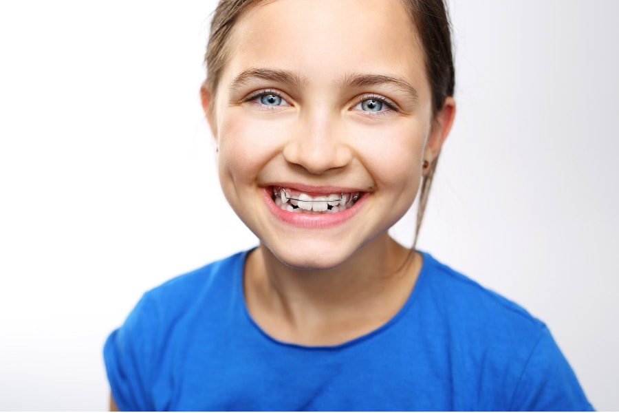 young girl smiling to show off her braces