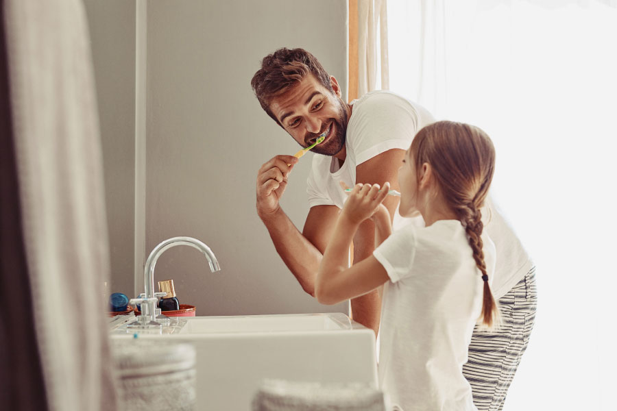 man brushing his teeth with his young daughter