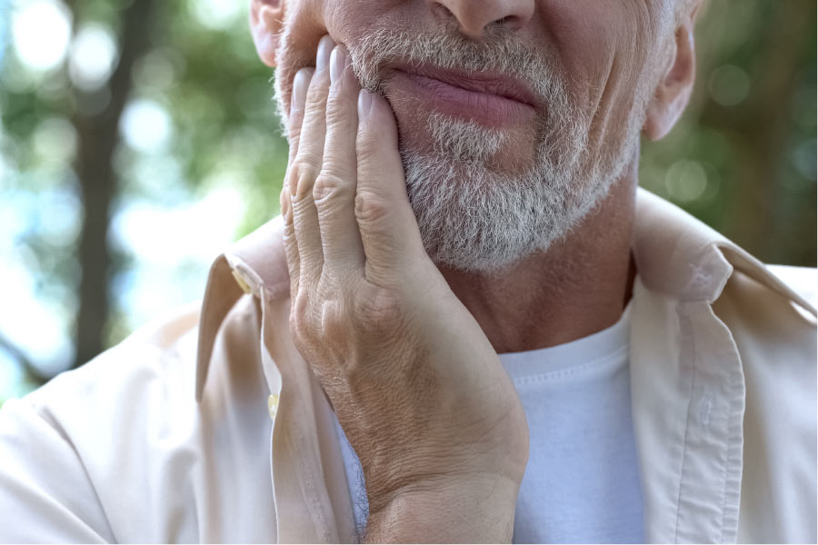 man with grey stubble holds his jaw in pain from TMJ/TMD