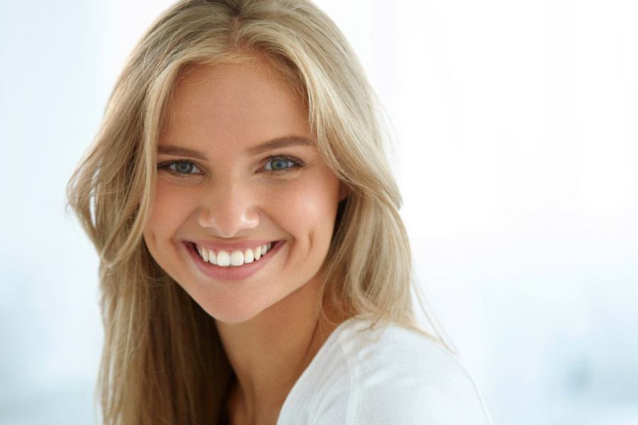 young woman smiles showing off her white teeth