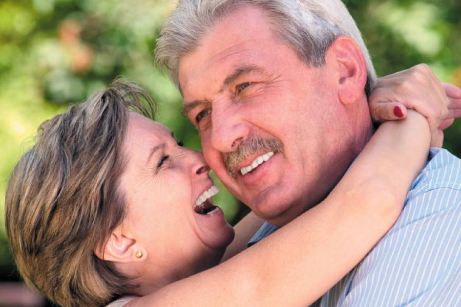 senior couple hug and smile after learning how versatile dental implants are