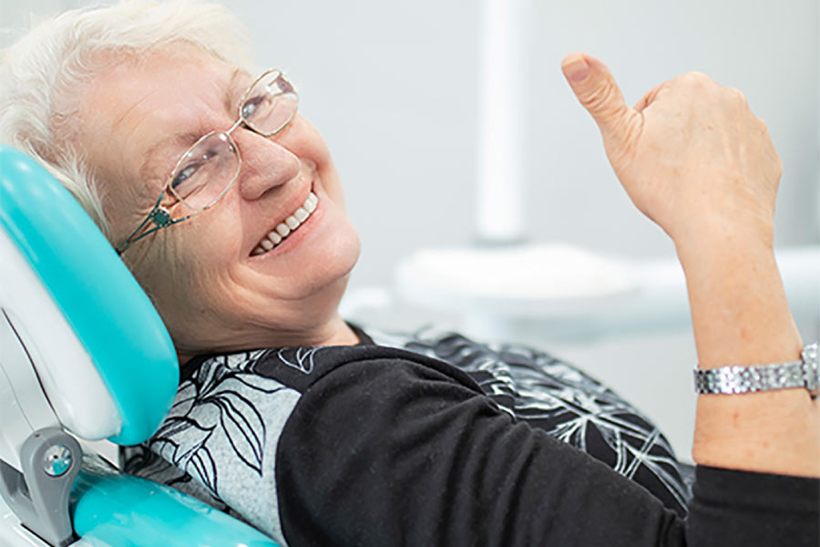 senior woman in the dentist's chair gives a thumbs up after getting a fixed dental bridge