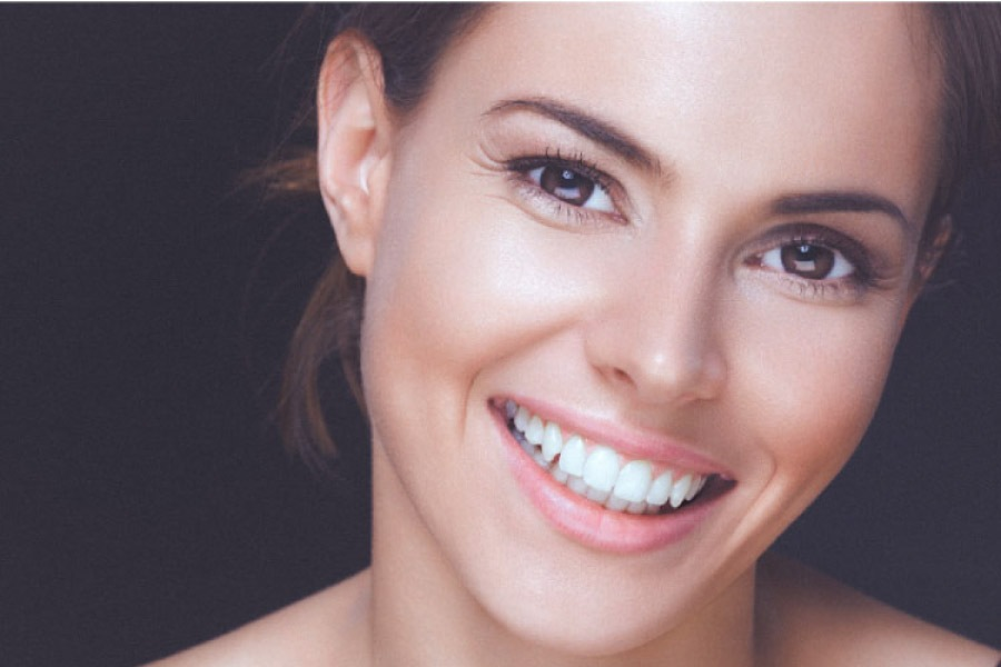 woman flashes a big smile showing off her porcelain veneers