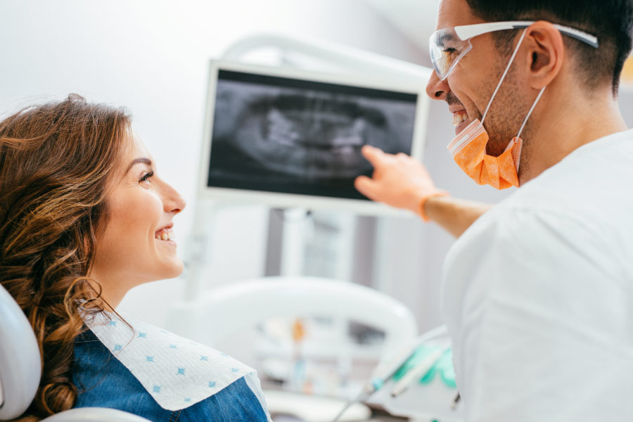 dentist and patient look at a digital x-ray to detect tooth decay
